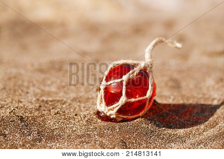 red Glass float on black beach sand