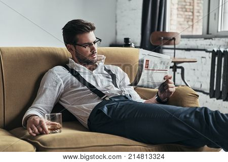 Interesting article. Stylishly dressed young man reading a newspaper and holding a glass while sitting on sofa