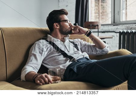 Feeling lonely. Thoughtful young man keeping hand on chin and looking away while sitting on sofa