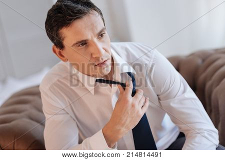 Leisure time. Responsible experienced worker sitting in a comfortable armchair and taking off his tie after having a long difficult exhausting day in his office