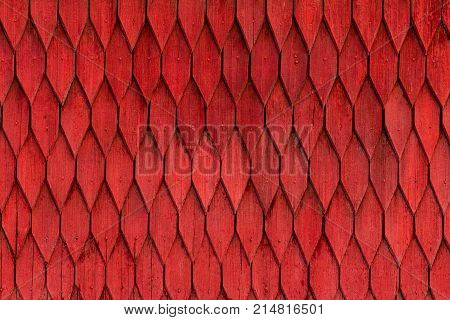 Old weathered wooden wall with ornament painted in red. Vintage texture Background.