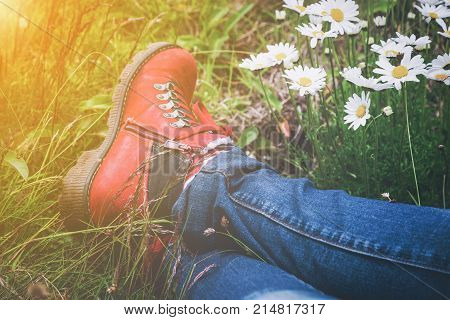 Person wearing hiking boots lying in a meadow with white spring daisies and golden glow from the sun in a close up view of the feet