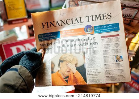 STRASBOURG FRANCE - NOV 21 2017: POV of male hand wearing gloves holding the Financial Times newspaper featuring news about Angela Merkel coalition election