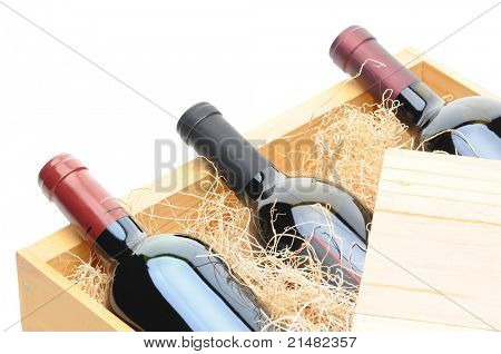 Closeup of three Cabernet Sauvignon wine bottles on their side in a wooden crate. Crate lid is pulled partially back exposing the bottles and packing excelsior. Horizontal format isolated on white.
