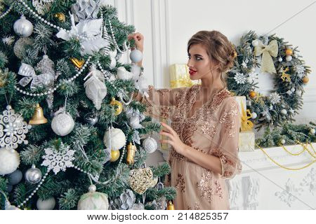 Merry Christmas and Happy New Year. Pretty young woman in evening dress decorates the Christmas tree. Beauty, fashion. Make-up, cosmetics.