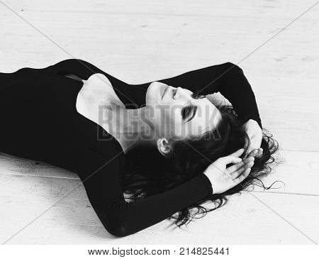 pretty cute sexy girl or young woman with fashion makeup on serious face and curly long brunette hair in black dress with deep neckline lying upside down with raised hands on wooden floor background