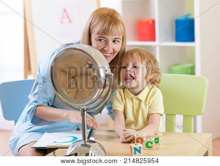 Child preschooler boy at speech therapist office. Kid makes tongue exercises together with teacher.
