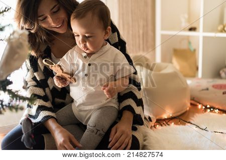 Mom And Baby Decorating The Christmas Tree.