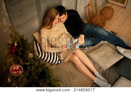 Pregnant woman with her husband sit before Christmas tree and look at baby's bootees. They keep them in hands.