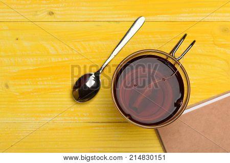 Glass Of Black Tea With Tea Bag Near Closed Book