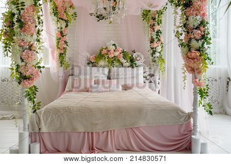 Honeymoon suite with canopy bed free space. Luxurious wood canopy bed with flowers and pillows on it. Female bedroom in pink and white colors copy space. Big comfortable bed in elegant bedroom