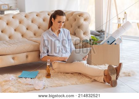 Busy woman. Hardworking busy woman sitting in front of a laptop and looking at the screen while a bottle of beer standing by her side