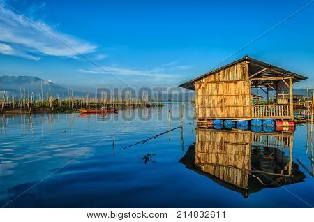 floating house above lake rawapening, this photo taken at sunrise, looks beautiful with the reflection of floating home from the lake