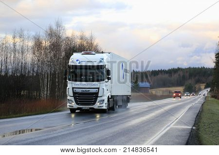 SALO FINLAND - NOVEMBER 4 2017: White DAF XF semi trailer of Mikko Niskala Oy transports goods along wet road in autumn dusktime in South of Finland.