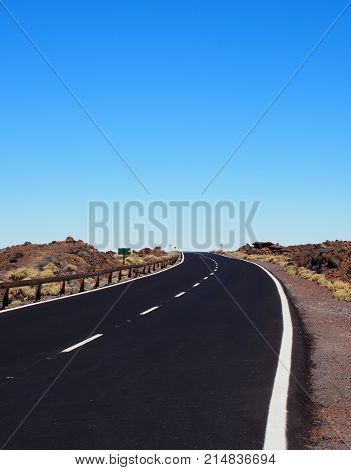 two lane empty road curving to the horizon in a rugged desert landscape with blue sky