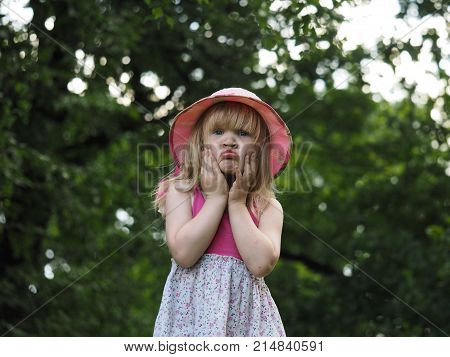 Portrait of a funny dirty little girl in a hat. The girl made a face