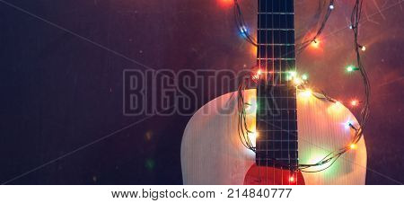 Old acoustic guitar with a garland on grunge background, Christmas sale of musical instruments