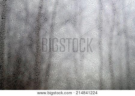 Dull landscape with many raindrops through house window on gloomy rainy autumn day
