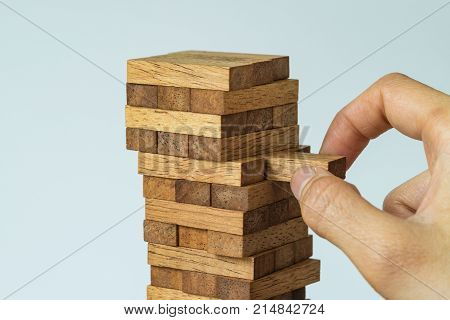 Risk or stability concept as female hand pulling wooden block from the tower.