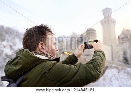 Handsome milddle age man making photo of famous royal castle Neuschwanstein. Happy winter weekend in the countryside. Vacation in mountains.