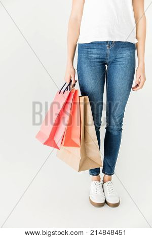 low section of young woman holding shopping bags isolated on white
