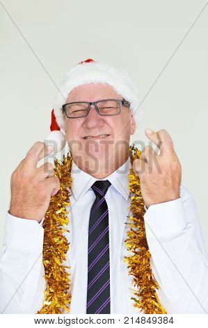 Portrait of anticipating senior Caucasian businessman wearing glasses, Santa hat and tinsel crossing fingers wishing good luck. Business Santa and Christmas giveaway concept