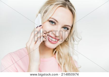 attractive young woman talking on smartphone and smiling at camera isolated on white