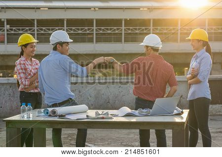 Fist Bumping Corporate Colleagues Teamwork between professional construction engineers after project complete at the sunset time Industrial engineering and teamworks Concept worm color tone