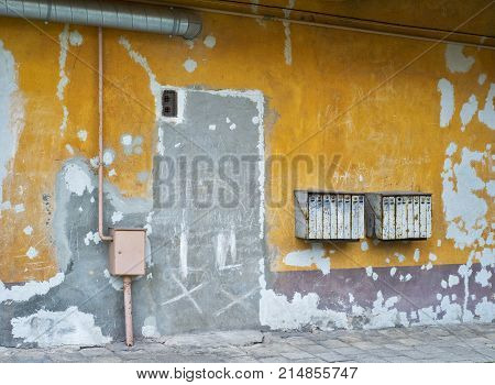 Rusty mailboxes on cracked yellow stucco wall