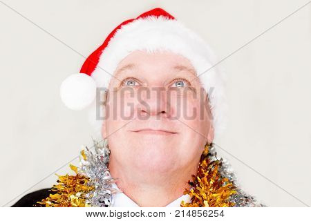 Content man wearing Santa hat in anticipation of New Year. Smiling dreamy businessman in costume looking up while making wish. New Year miracle concept
