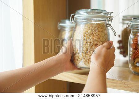 Hands picking macaroni in glass jar for preparing food