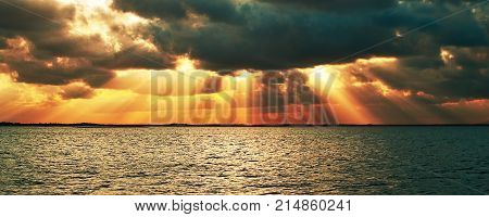 Dark storm cloud sea water tropical panoramic sunset seascape featuring golden crepuscular rays with ocean water reflections. Queensland Australia.