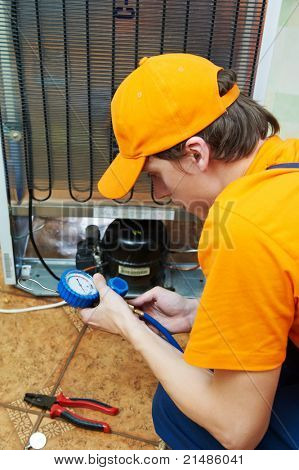 Repairman makes refrigerator appliance troubleshooting and maintenance works