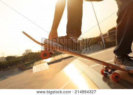 young skateboarder legs skateboarding on skatepark ramp