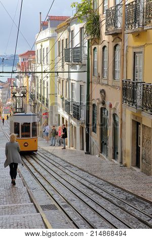 LISBON, PORTUGAL - NOVEMBER 4, 2017: The funicular Elevador da Bica in Bairro Alto neighborhood with colorful facades and Tagus river in the background