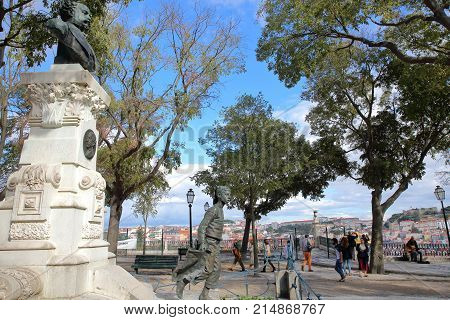 LISBON, PORTUGAL - NOVEMBER 4, 2017: Sao Pedro de Alcantara viewpoint (Miradorou) in Bairro Alto neighborhood with a monument to Eduardo Coelho in the foreground