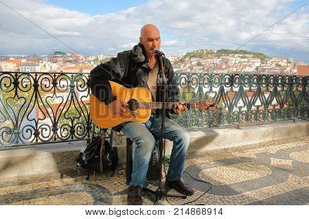 LISBON, PORTUGAL - NOVEMBER 4, 2017: Portrait of a musician singer at Sao Pedro de Alcantara viewpoint (Miradorou) in Bairro Alto neighborhood with the city in the background