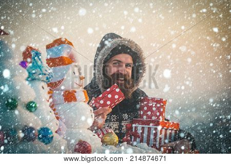 Happy Man With Gift Boxes On Snowy Landscape