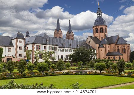 Colorful bright cityscape. Ancient monastery Seligenstadt : Basilika Saint Marcellinus and Petrus Benedictine abbey and garden and formal park against cloudy blue sky. Germany. Tourist destination