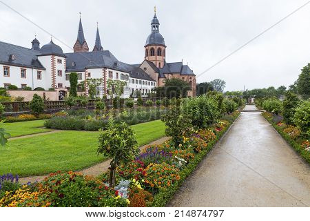 Colorful cityscape. Ancient monastery Seligenstadt : historic baroque building Basilika Saint Marcellinus and Petrus Benedictine abbey and vegetable garden and formal park. Germany. Tourist destination