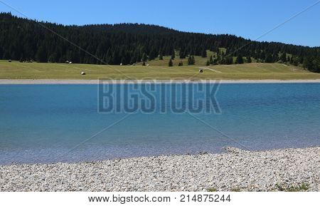 beautiful alpine pond with crystal clear water and mountains in the background