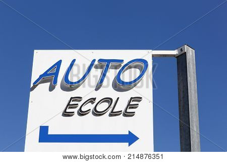 Driving school sign in French with a blue sky