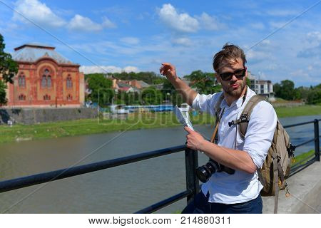 Traveller on river bank trying to find way. Man with serious face on blurred cityscape background. Travelling and navigation concept. Tourist on the street holds guide or map and points at building