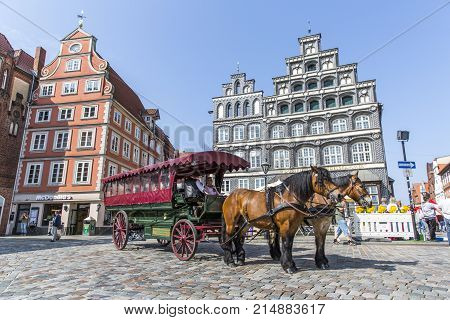 LUNEBURG, GERMANY - MAY 28, 2016: Horse-drawn coach on the historic square in Luneburg