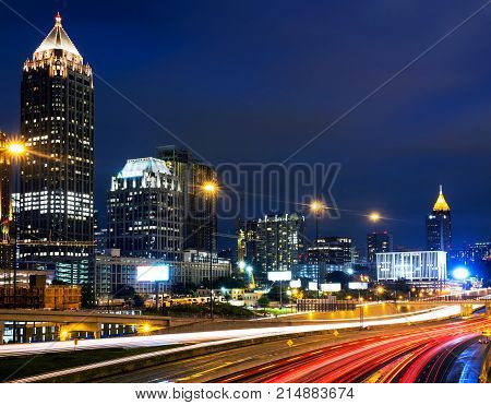 Atlanta USA. Illuminated Midtown in Atlanta USA at night. Car traffic illuminated buildings and dark sky. Car traffic trails
