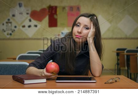 Tired and bored young female student girl sits at a desk in the school classroom holding in hands an and wants to sleep. Education concept.