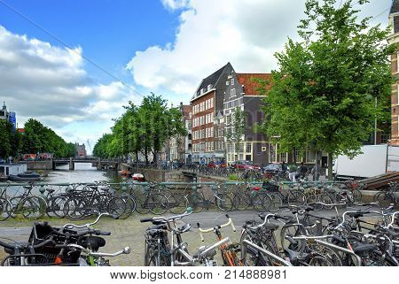 AMSTERDAM, JUN.15, 2010: Summer view on bridge with many bikes old classic Holland houses buildings at water channel Many bikes at bike parking in Holland on bridge. Many bicycles on European streets