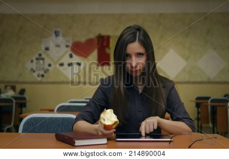 Caucasian young female student girl is sitting at a desk in the school classroom holds and eats and reads lecture in her tablet computer pc or looking for information. Education concept.