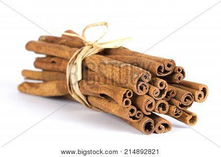 A fragrant spice. long cinnamon on a white background with soft shadow. Dried wood bark on isolated.