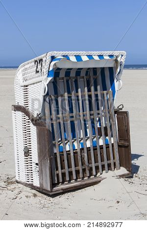 Image shows a beach chair without people in the sun